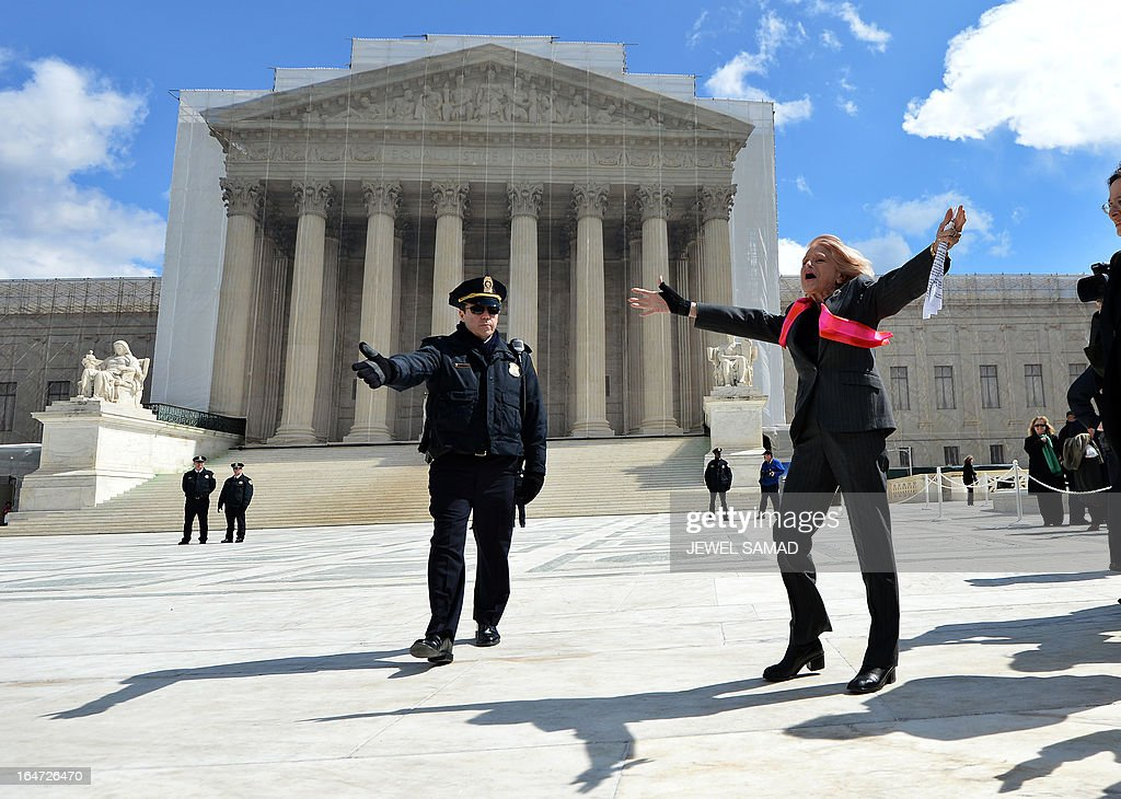 Plaintiff Edie Windsor (R), an 83-year-old lesbian widow, gestures at same-sex marriage supporters as she leaves the Supreme Court on March 27, 2013 in Washington, DC, after the US v. Windsor case hearing challenging the constitutionality of Section 3 of the Defense of Marriage Act (DOMA). The US Supreme Court tackled same-sex unions for a second day Wednesday, hearing arguments for and against the 1996 US law defining marriage as between one man and one woman. After the nine justices mulled arguments on a California law outlawing gay marriage on Tuesday, they took up a challenge to the constitutionality of the federal Defense of Marriage Act (DOMA). The 1996 law prevents couples who have tied the knot in nine states -- where same-sex marriage is legal -- from enjoying the same federal rights as heterosexual couples. AFP PHOTO/Jewel Samad