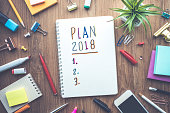Plan 2018 message with notepad paper on wooden table and supplies.Business plan concepts.flat lay design