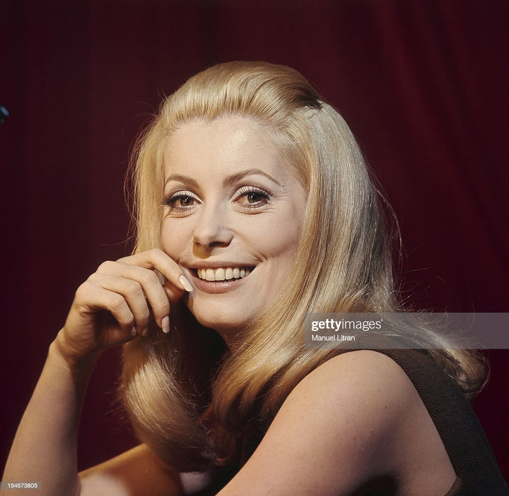 Plan smiling face of <a gi-track='captionPersonalityLinkClicked' href=/galleries/search?phrase=Catherine+Deneuve&family=editorial&specificpeople=123833 ng-click='$event.stopPropagation()'>Catherine Deneuve</a> in brown sleeveless dress, one hand on the cheek during a break in the filming of 'Beautiful Day' by Luis Bunuel.