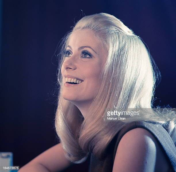 Plan smiling threequarters of Catherine Deneuve in brown sleeveless dress looking up during a break in the filming of 'Beautiful Day' by Luis Bunuel