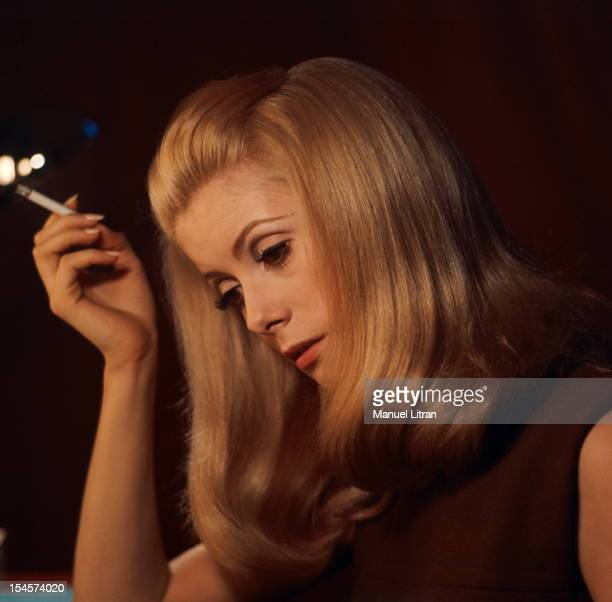 Plan threequarters of Catherine Deneuve in brown sleeveless dress head tilted a cigarette in his hand during a break in the filming of 'Beautiful...