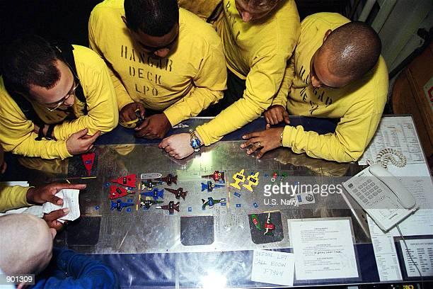 Plane directors plan aircraft movement around 'The Ouija Board' a tabletop model of the aircraft carrier's flight deck December 12 2001 at sea aboard...