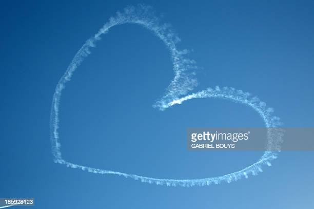 A plane draws a heart in the sky of Los Angeles on October 12 2013 Skywriting messages are usually used to have a sky high marriage proposal or...