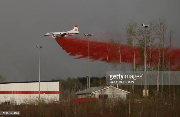 A plane drops fire retardant near a building near a road block on Highway 63 near Fort McMurray Alberta on May 6 2016 Canadian police led convoys of...