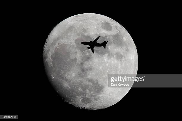 A plane flies across the moon on April 26 2010 in London England