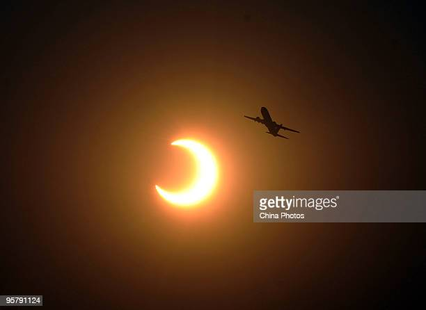 A plane flies in front of a partial solar eclipse at the Tianfu Square on January 15 2010 in Chengdu of Sichuan Province China An annular eclipse of...