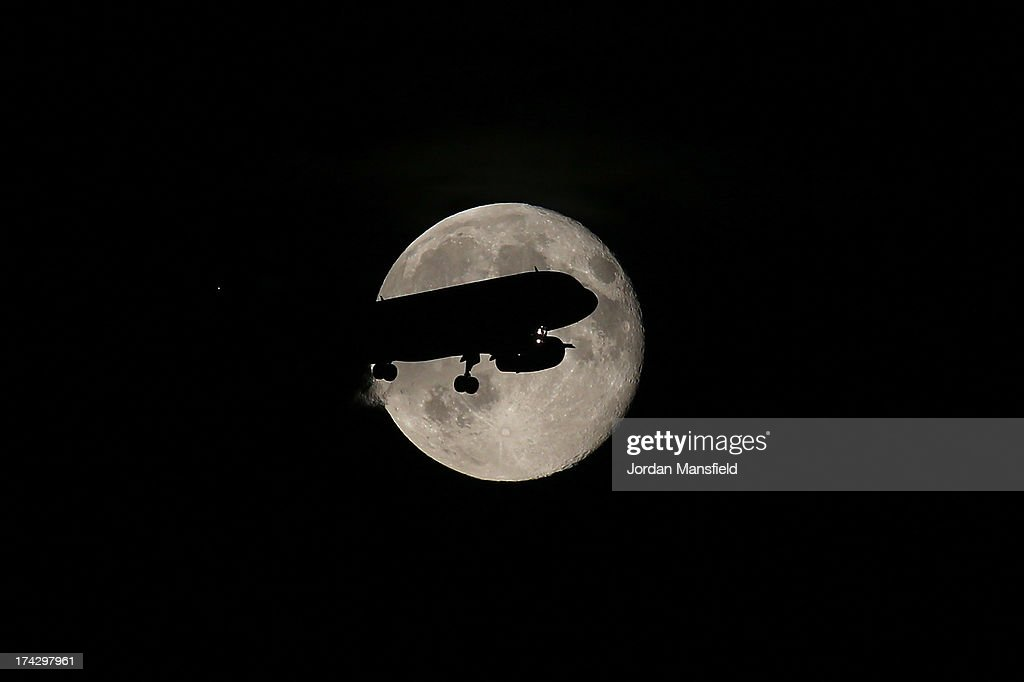 A plane flies in front of the moon July 23, 2013 in Horley, England.