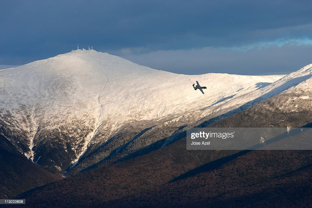 A plane flies in the distance over Mt. Washington and the Presidential Range .