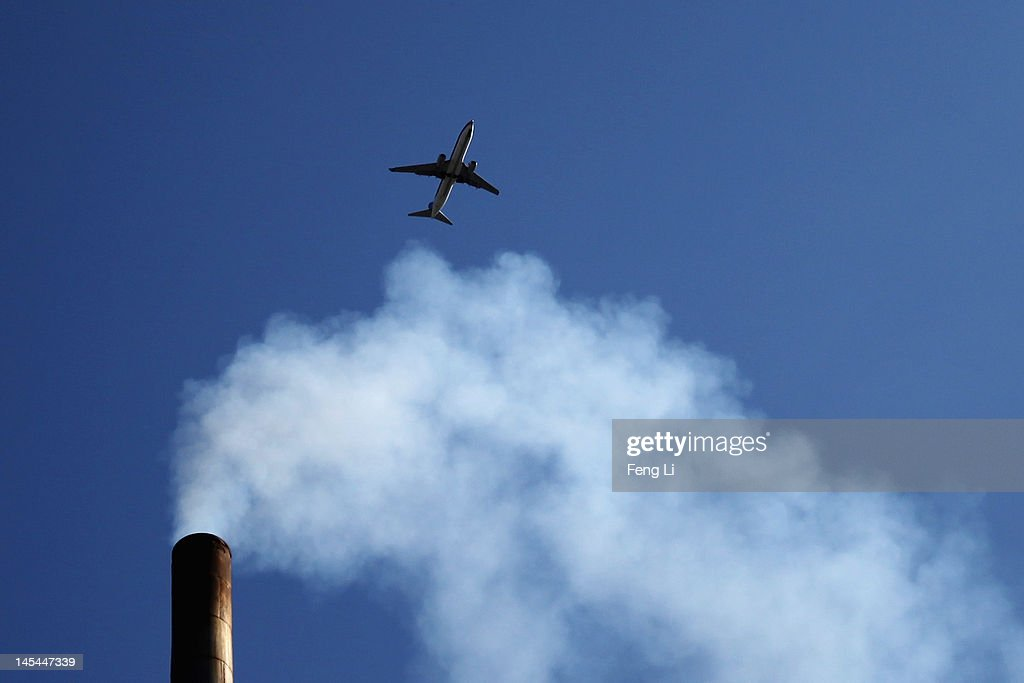 A plane flies over a chimney on May 30, 2012 in Beijing, China. The State Council of China adopted a plan to boost the development of seven strategic emerging industries amid the country's economic slowdown on Wednesday. According to the statement, the strategic industries include energy-saving and environmental protection, information technology, biology, advanced equipment manufacturing, new energy, new materials and new-energy vehicles.