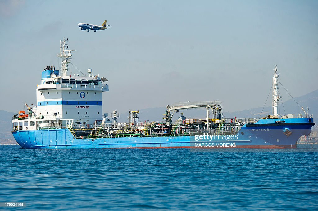 A plane flies over a ship waiting for an offshore refueling in the bay of Algeciras, near Gibraltar, on August 16, 2013. Madrid is threatening to take action against Gibraltar's offshore refueling of ships, adding a new front in its row with London over contested waters around the British outpost on Spain's southern tip. Due to a lack of space on land to store fuel tanks, Gibraltar has tankers permanently anchored in its bay that store fuel which is then delivered by pipe to ships that dock beside them.