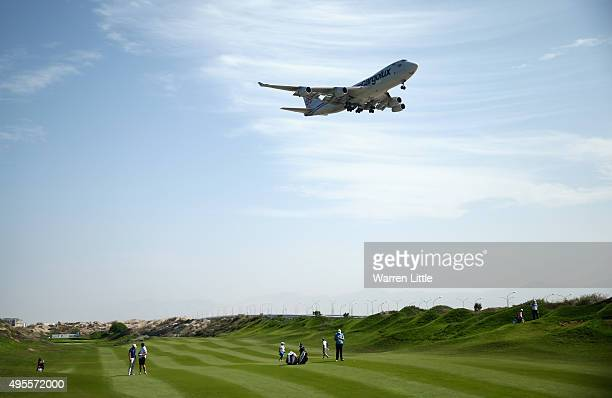 A plane flies over the 16th fairway during the first round of the NBO Golf Classic Grand Final at the Almouj Golf Club The Wave on November 4 2015 in...