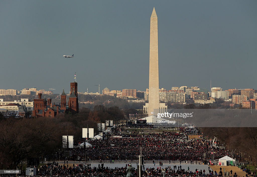A plane flies overhead as people gather near the Washington monument before the start of the U.S. presidential inauguration in Washington, D.C., U.S., on Monday, Jan. 21, 2013. As he enters his second term President Barack Obama has shed the aura of a hopeful consensus builder determined to break partisan gridlock and adopted a more confrontational stance with Republicans. Photographer: Scott Eells/Bloomberg via Getty Images