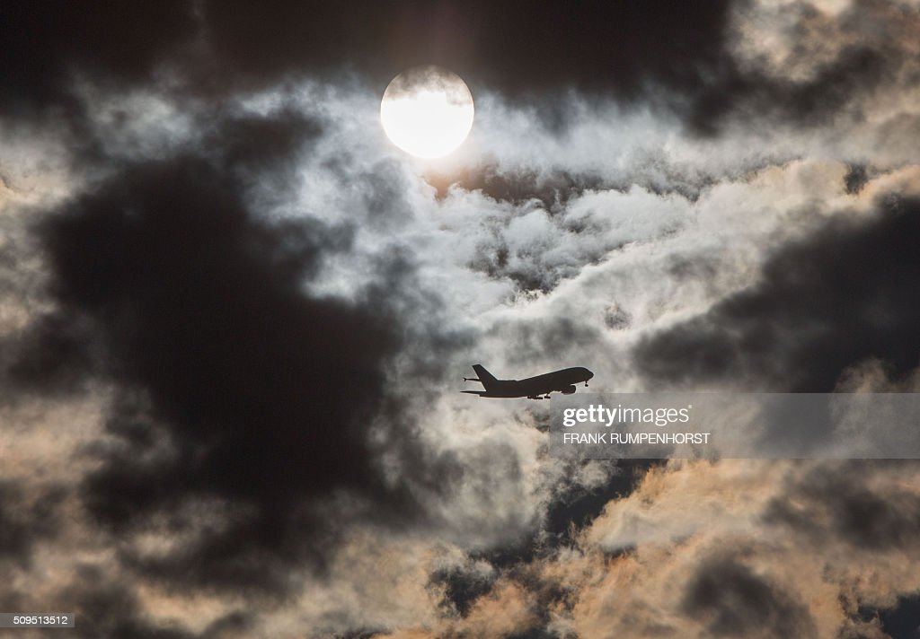 A plane flies through the morning sky past the sun hidden behind clouds on February 11, 2016 in Frankfurt am Main, western Germany. / AFP / dpa / Frank Rumpenhorst / Germany OUT