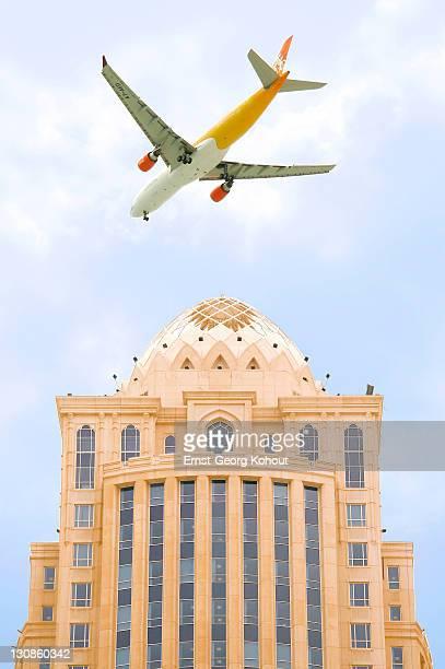 Plane flying above hig-rise building, Doha, Qatar, Arab Emirates