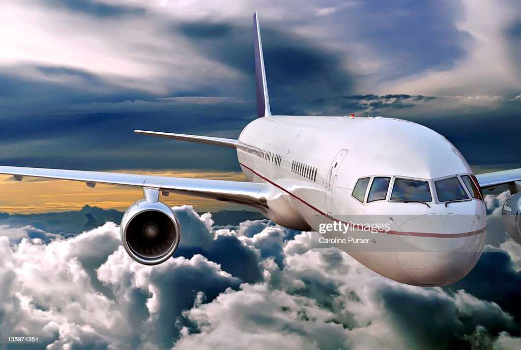 Plane flying in the clouds : Stock Photo