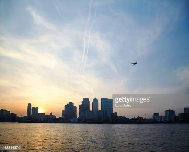 Plane flying over London skyline.