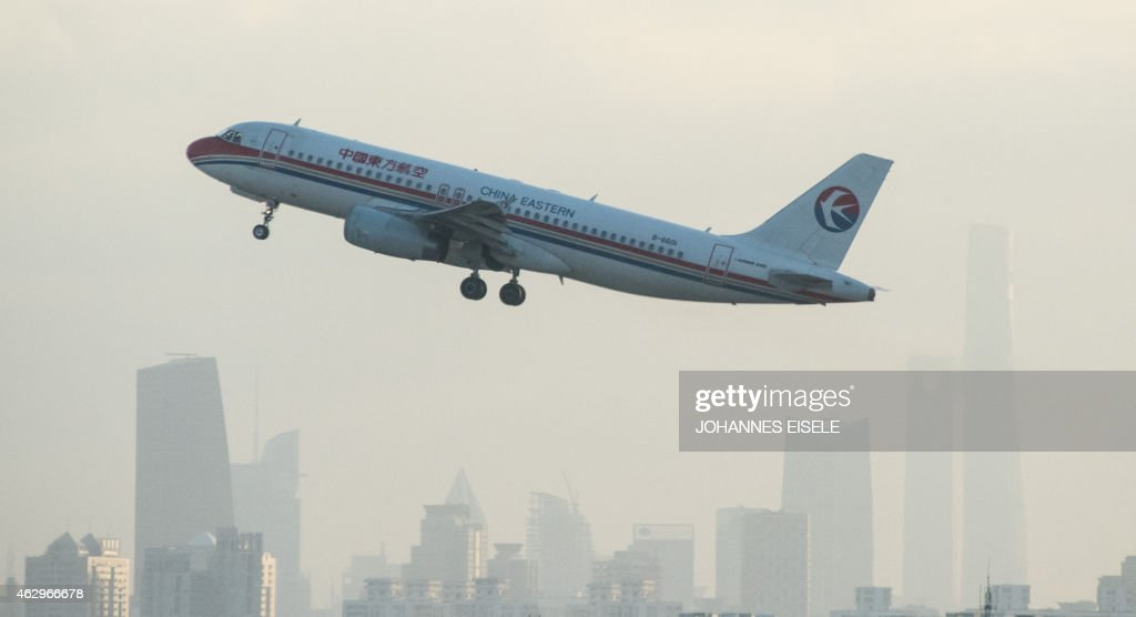 A plane from Chinese airline China Eastern departs from Hongqiaou Airport in Shanghai in front of the skyline on February 8 2015 AFP PHOTO / JOHANNES...