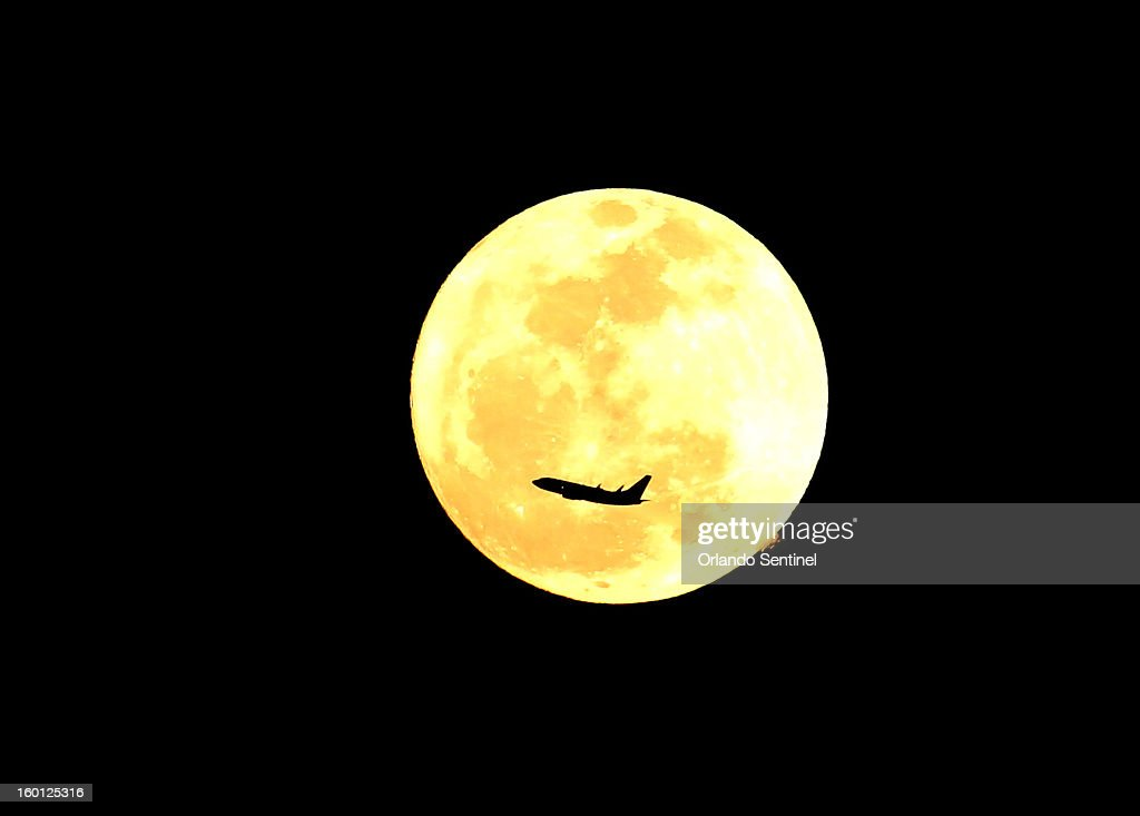 A plane from Orlando International Airport crosses a full moon upon takeoff in Orlando, Florida, on Saturday, January 26, 2013.