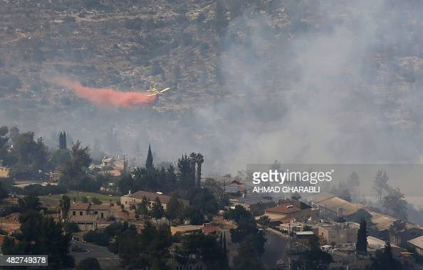 A plane from the Israeli fire service sprays flame retardant chemicals as it tries to extinguish a large forest fire that raged out of control in the...