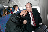Plane Interior, Man Falling Asleep on the Embarrassed Businessman Next to Him