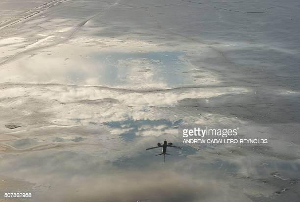 TOPSHOT A plane is reflected as it comes in for a landing over the frozen Potomac river in Washington DC on February 1 2016 / AFP / Andrew...