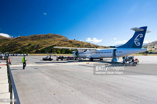A plane lands at the Queenstown airport. It has the old fashioned feel as you walk from the plane to the terminal