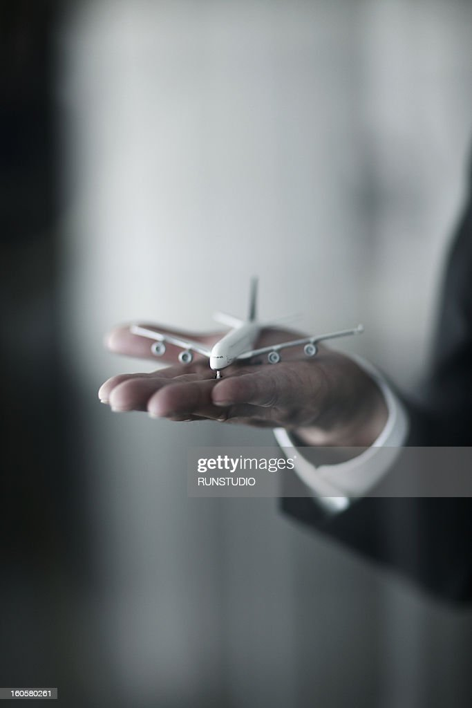 A plane model on a business man's hand : Stock Photo