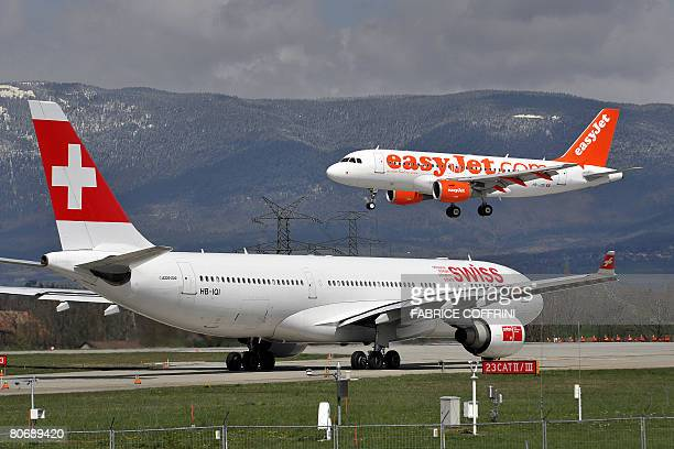A plane of low cost airline Easyjet lands behind a plane of Swiss International Air Lines at the Geneva international airport on April 15 2008 AFP...