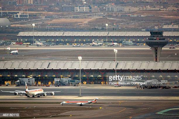 A plane operated by Iberia passes by the tower control at Madrid Barajas Adolfo Suarez airport on February 11 2015 in Madrid Spain Shares in...