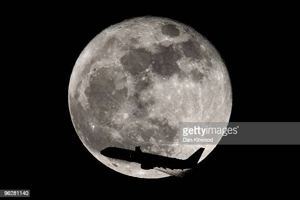 A plane passes the moon on January 30 2010 in London England Tonight sees the biggest and brightest moon of 2010 also called the wolf moon appearing...