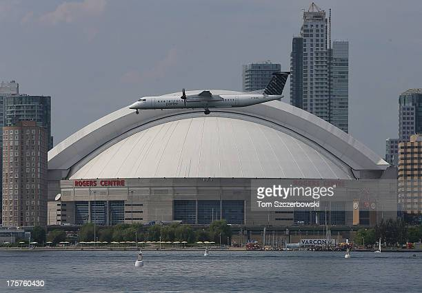 A plane prepares to land at the Toronto City Centre Airport as the Rogers Centre can be seen from the Toronto Islands on Lake Ontario on July 18 2013...