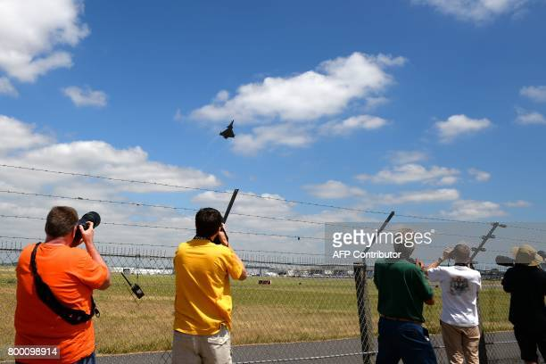 Plane spotters take pictures and videos of a Dassault Aviation Rafale jet fighter as it takes off during the International Paris Air Show in Le...