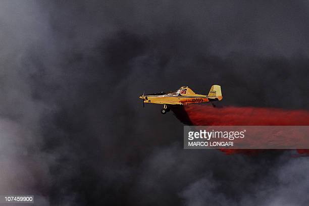 A plane sprays the retardant chemical used to quell the latest front of the raging flames near the village of Ussafiya in Haifa's Carmel forest on...