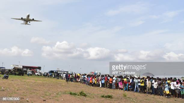 A plane takes off as people stand on the beach of PortBouet in Abidjan near the wreckage of a cargo plane that crashed off Ivory Coast killing four...