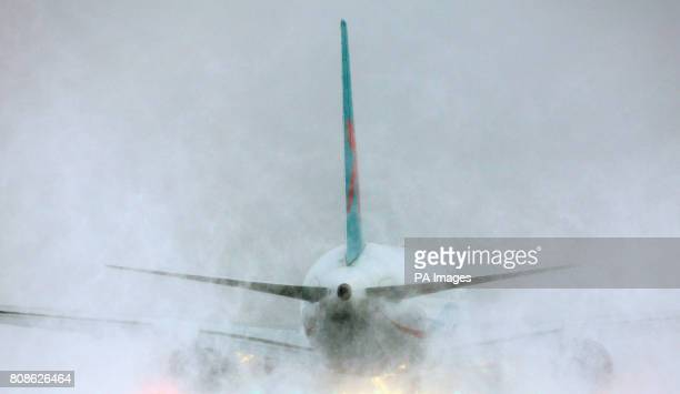 A plane throws up clouds of snow as it prepares for take off at Gatwick Airport in West Sussex following the airport reopening after it was closed...