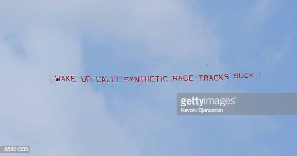 A plane towing a banner protesting against Santa Anita track's synthethic turf flies during the 72nd running of the Santa Anita Derby on April 4 2009...