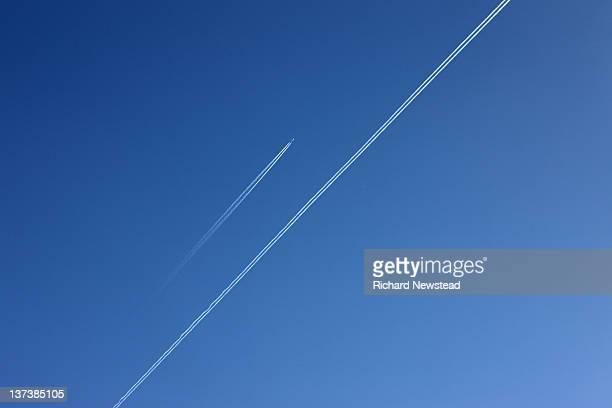 Plane vapor trails in blue sky