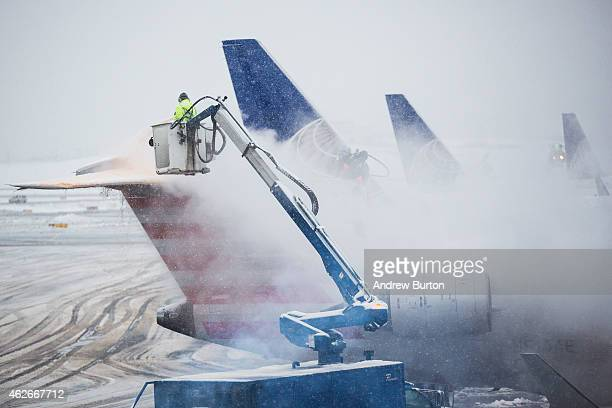 Planes are deiced at La Guardia Airport during a winter storm on February 2 2015 in the Queens borough of New York City The snowstorm which is...