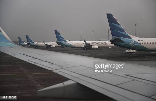 Planes are seen parked on the tarmac of Jakarta's International airport in Tangerang on October 25 as haze looms over the capital city Indonesia has...