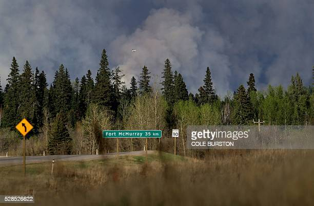 Planes fly overhead as smoke billows in the sky near Fort McMurray Alberta on May 5 2016 The Province of Alberta has issued a State of Emergency as...