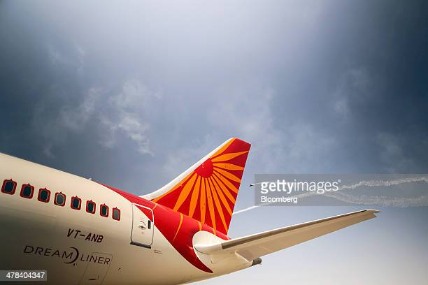 Planes fly past a Boeing Co 787 Dreamliner aircraft operated by Air India Ltd on display during the India Aviation 2014 air show held at the Begumpet...