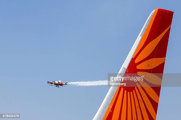 Planes fly past the tail of a Boeing Co 787 Dreamliner aircraft operated by Air India Ltd on display during the India Aviation 2014 air show held at...