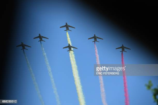 Planes leave trails in the colours of the Belgian flag during a NATO summit ceremony at the NATO headquarters in Brussels on May 25 2017 / AFP PHOTO...