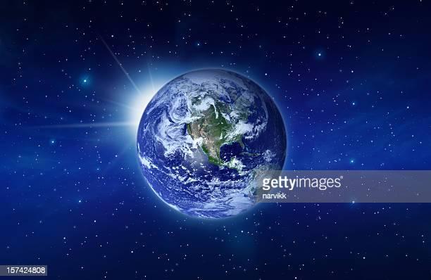 Planet Erde mit der aufgehenden Sonne hinter