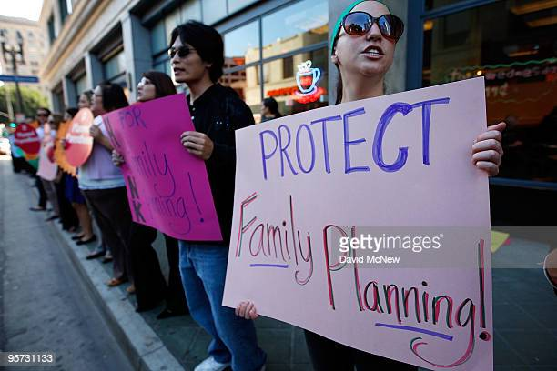 Planned Parenthood patients volunteers and supporters rally outside the office of Assembly Speakerelect John Perez to oppose cuts to family planning...