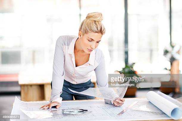 Planner Analyzing Blueprint At Desk