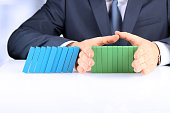 Planning, risk and strategy in business, businessman  holding   wooden blocks.  Businessman Stopping The Effect Of Domino