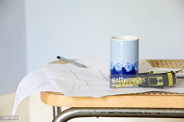 Plans on chair with tape measure and mug