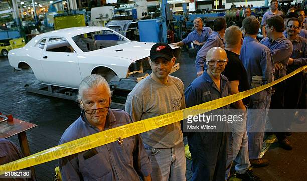 Plant workers stand near a the body of a Dodge Challenger while waiting for Democratic presidential hopeful Sen Barack Obama as he tours the Chrysler...