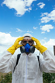 Industrial agriculture theme. Portrait of man with protective mask spraying toxic pesticides or insecticides on fruit growing plantation. Natural hard light on sunny day. Blue sky with clouds in backg